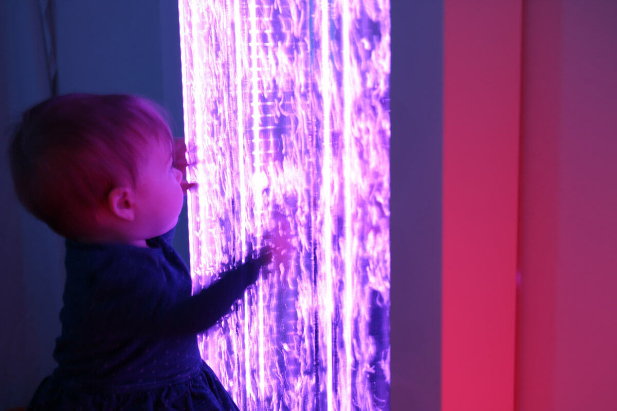Molly plays with a sensory bubble wall